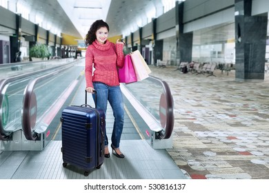 Happy indian woman wearing winter clothes and standing in the airport hall while carrying suitcase and shopping bags