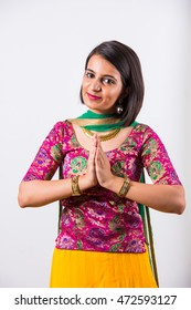 Happy indian young girl in ethnic lehengas in namaskara or welcoming pose , isolated over white background.