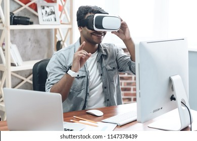 Happy Indian Young Man at Home in VR Glasses Using Virtual Vision Watching Reality Simulation and Play Games. Digital Fun Concept. Software Technology of Simulation. Future Technology Concept.