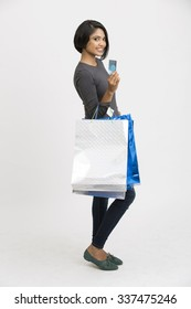Happy Indian young woman with shopping bags and credit card