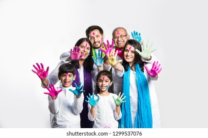 happy Indian/asian family celebrating Holi festival with colours. Multi generation people standing isolated over white background. selective focus