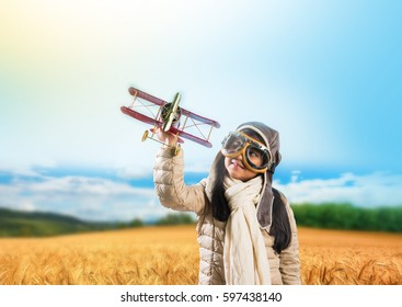 Happy Indian/asian girl kid/child playing with toy metal airplane against winter sky background