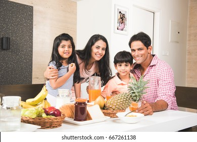 Happy Indian/Asian Young family Dining at home and having fun. selective focus