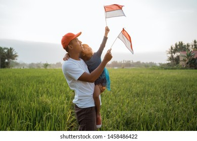happy indonesian kid and her father with national flag outdoor