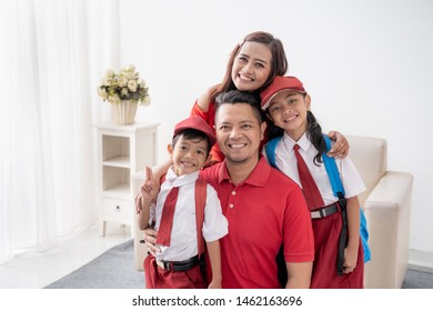happy indonesian student with uniform smiling to camera with parent