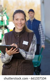 happy industrial female inspector worker with clipboard at factory