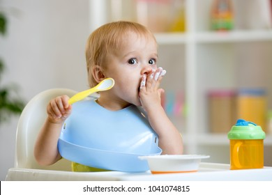 Happy infant baby boy spoon eats itself