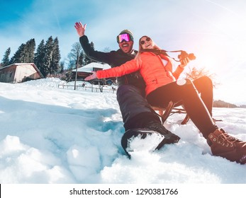 Happy influencers couple having fun with wood vintage sledding on snow high mountains - Young crazy people enoying winter vacation - Travel and holiday concept - Focus on faces