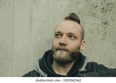 happy inspired bearded man looking up in front of a wall