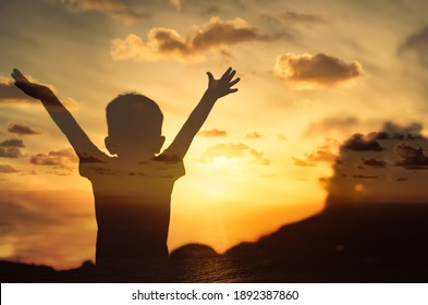 Happy and inspired little child with arms up looking to the sunset. Double exposure.