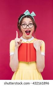 Happy inspired young woman in glasses with red book pointing up and having an idea over pink background