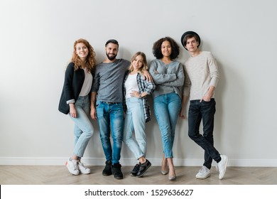 Happy intercultural guys and girls in casualwear standing against white wall in front of camera