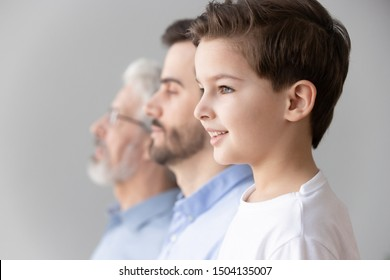 Happy intergenerational muti 3 three generation men family portrait, cute child boy son grandson looking forward think dream of future stand in row with young father and old grandfather, side view