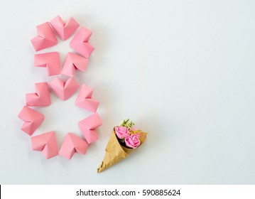 Happy International Women's Day celebrate on March 8, congratulatory CARD. rose-color paper hearts shape figure eight 8 on white background