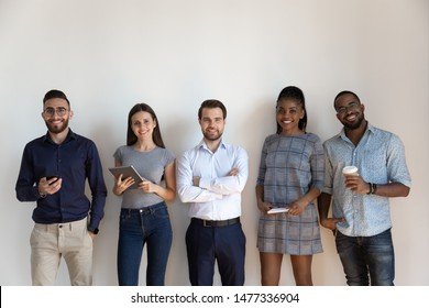 Happy international professional business people standing in row near wall looking at camera, smiling multiracial young human resource corporate staff group or successful team portrait, hr concept
