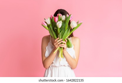 Happy International Women's Day Concept. Unrecognizable Girl Holding Tulips Bouquet, Covering Her Face, Posing Over Pink Studio Background, Free Space