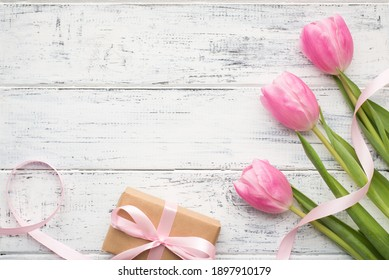 Happy international women's day concept. Photo of nice tulips with tender pink ribbon and wrapped in kraft paper giftbox on wooden desk with empty space