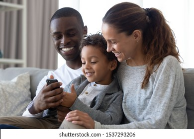 Happy international young family with little son sit on couch watching cartoons on cellphone together, smiling multiracial parents relax on couch at home with biracial boy child using smartphone