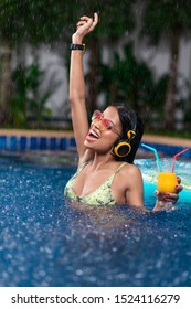Happy interracial brunette enjoys in the pool with a cocktail in her hand, in yellow headphones and a wristwatch, yellow-pink sunglasses raised by her hand, a green bikini. Rain. Drops of water.
