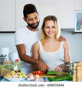 Happy interracial couple cooking vegetables and laughing in kitchen