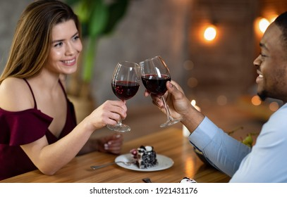 Happy interracial couple with glasses of red wine having date in restaurant, making toast for love. Affectionate multicultural lovers enjoying romantic dinner, celebrating valentine's day together