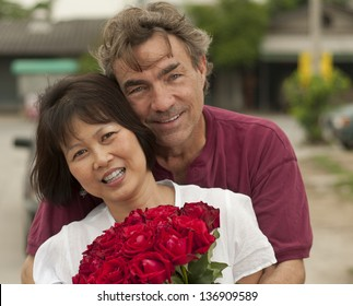 Happy interracial couple hugging with roses