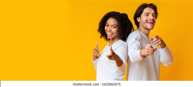 Happy interracial couple pointing at camera with both hands and laughing, posing together over yellow background, panorama with empty space