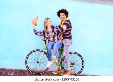 Happy interraziales Paar auf blauem Hintergrund auf blauem Himmelswall Rad fahren - Spielerfreunde auf Fahrradtour, die zusammen Spaß haben - Konzept von gesundem Lebensstil und Reisen in gekachelter Komposition