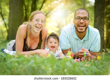 Happy interracial family is enjoying a day in the park. Mother father and mulatto son are smiling and are picnicking in the green park. Soft focus or shallow depth of field.