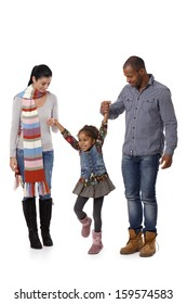 Happy interracial family with little girl walking, jumping, having fun.