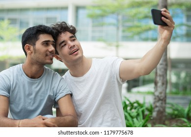 Happy interracial gays posing for cute selfie in city. Cheerful young friends in t-shirts photographing together against university building. Relationship concept