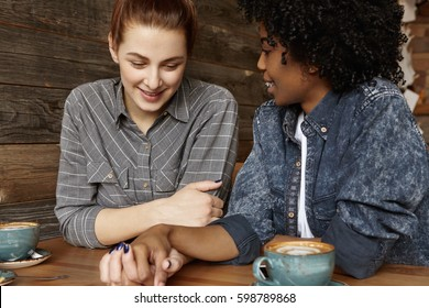 Happy interracial lesbian female couple relaxing at cafe during lunch: attractive woman with ginger hair looking down and smiling after saying yes to marriage proposal of her dark-skinned girlfriend