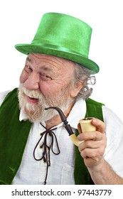 Happy Irish leprechaun with white beard, top hat, green velvet vest, and curved pipe in hand. He raises eyebrows, smiles and tilts head. Isolated on white, vertical layout with copy space.