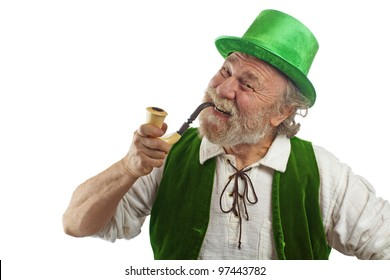 Happy Irish leprechaun with white beard, top hat, green velvet vest, and curved pipe in mouth. He raises eyebrows, smiles and tilts his head. Isolated on white, horizontal layout with copy space.