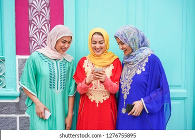 Happy islamic frends using smartphone - Young arabian girls having fun with new social app outdoor - Technology, influencer and friendship concept - Focus on faces
