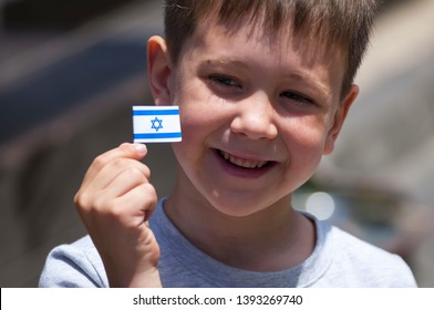 Happy Israeli Caucasian Jewish child with a tiny flag of Israel in his hands. Israeli kid celebration the Independence Day of Israel.