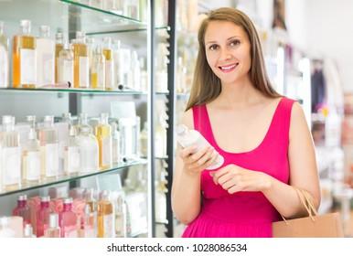 happy italian female choosing perfume conditioner in shopping mall