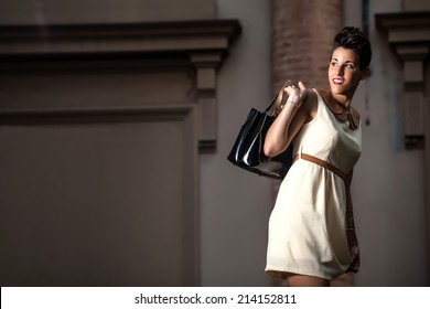 happy italian young modern caucasian lady with short hair with elegant dress and with purse in hands walking on the streets