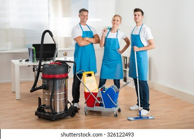 Happy Janitors With Vacuum Cleaner And Cleaning Equipments In Office