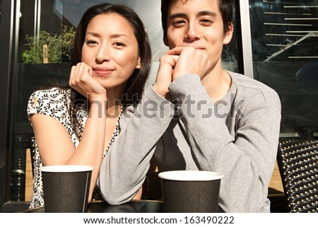 Happy Japanese couple sitting together at a coffee shop terrace having a hot coffee beverage and leaning on their hands while smiling at the camera during a sunny day, outdoors.