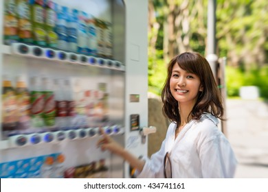 Happy japanese girl choosing soft drink at city machine.