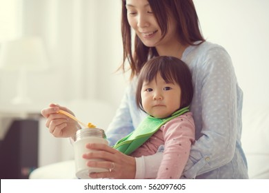 Happy japanese mother feeding her little cute daughter with spoon at home