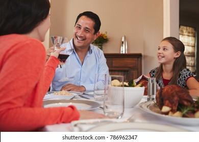 Happy Jewish family raising glasses before Shabbat meal