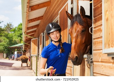 Happy jockey girl with bay horse by riding stables