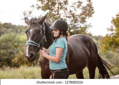 A happy jockey girl taking care and leading her favorite horse. The girl loves animals and horseback riding.