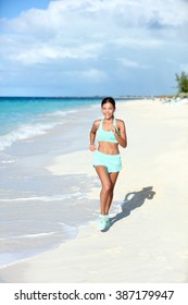Happy jogging woman running on sunny beach living a fit and active life. Happiness and health concept on summer vacation travel beach.