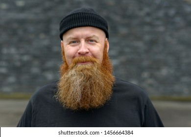 Happy jovial bearded redhead man wearing a black beanie hat grinning at the camera with a mischievous expression