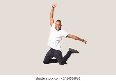 Happy joyful african american guy jumping high with raised hand and bent in knees legs between softbox lights on grey studio background, professional male model having fun during photo shooting