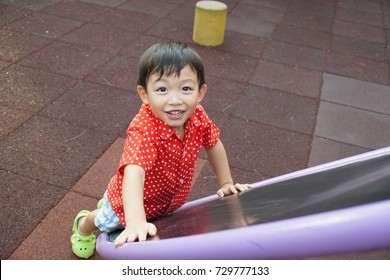 Happy and joyful big eyes black hair Asian boy/kid in red and white dotty shirt/Christmas theme costume playing in the park