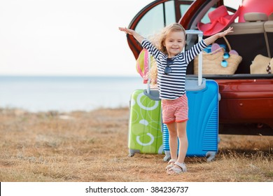 happy and joyful child in car and suitcases background. vacation and car trip concept. freedom and wind. girl traveler. holidays, voyage, sea and beach on background. summer time